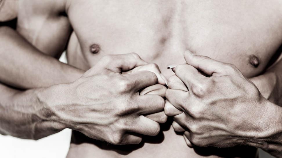 Женщина ласкает мужскую грудь